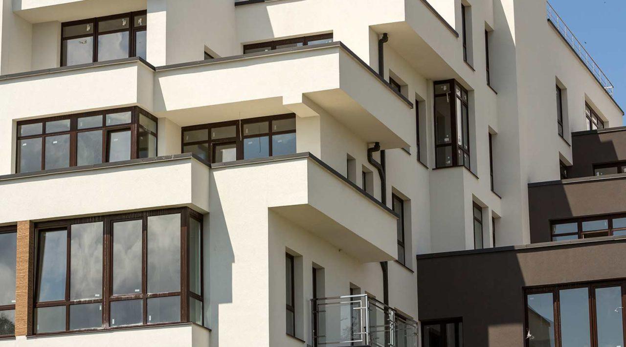 Neubau Wohnungen mit Terrassenbalkonen glänzende Fenster geschützter Zaun Flachdach